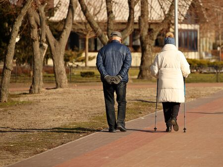 Elderly couple on a walk with sticks for Nordic walking. Healthy and active lifestyle of retirees. Family outdoor recreation. Wellness walking to speed up metabolism and lose weight. Happy old age. Stock Photo
