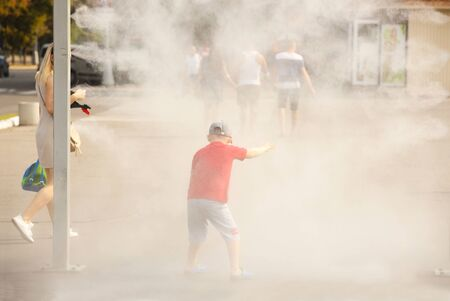 A children in summer goes through the frame of a refreshing street shower. Use fine water dust during the hot season to refresh pedestrians. Protection against overheating and sunstroke by splashin. Stock Photo