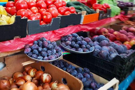 A variety of vegetables and fruits lying on a market counter for sale by a customer. Trade in agricultural products. Nitrates and pesticides. Genetically modified food. Farm fruits. Fiber and vitamins.