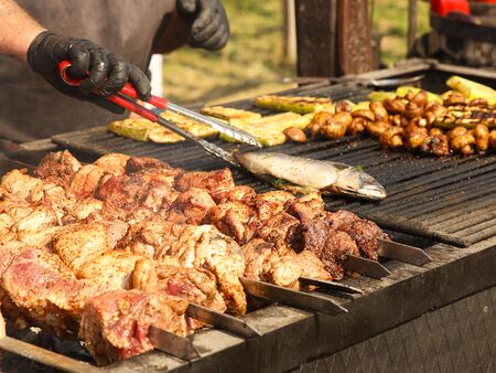 A man is cooking barbecue on an open fire. The cook flips the baked fish. Grilled meat and ribs. Fatty high-calorie foods with cholesterol. Cooking on the street. A dish of national cuisine from wild.