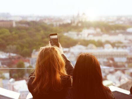 Two girls take a panorama photo of the ancient city with a smartphone. An observation deck at the town hall of the central Rinok square of the city of Lviv in Ukraine. Tourist selfie place on sunset .