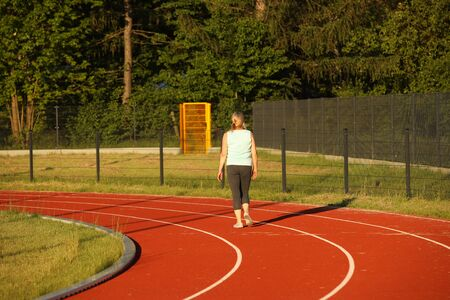 A woman runs on the treadmill of a stadium around a football field. Artificial cover of the sports complex. Activity for weight loss and a healthy lifestyle. Preparing for the competition. Free time.