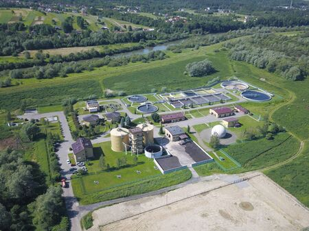 Urban sewage treatment plant. Aerial photography of sewage treatment plants located among beautiful green hilly terrain. Recycling human waste. The issue of clean drinking water.