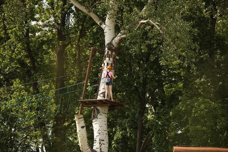 Yaslo, Poland - 8 7 2019:A young girl climbs the trees in gear in a park for rock climbing. Scandinavian attraction for sports events. Rope insurance and means of protection. Safety at altitude Stock Photo