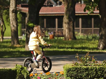 A little girl riding a bike in the park with safety wheels. Active development of the child in the fresh air. Learning to keep balance in transport management. Two-wheel balancing. Joyful childhood.