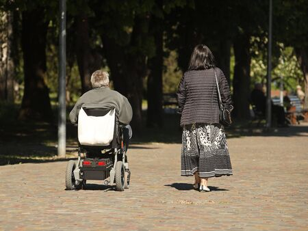 A woman is walking in the park with a man who is traveling on an electric wheelchair. Custody of the needy. The activity of people with limited mobility. Prosthetics of patients of the musculoskeletal system.