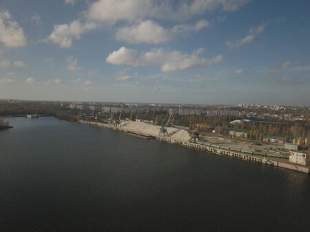 Grain elevator in the port on the river bank. Huge stainless steel tanks for storing crops. Aerial drone or quadrocopter aerial view. Agro-industrial business. Agriculture. Modern farm in Ukraine