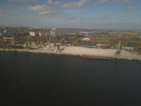 Large port cranes on the shore near the pier unload the river sand barge onto a large heap. The train for the transport of bulk cargo. The work of the cargo port. Aerial photography drone quadrocopter