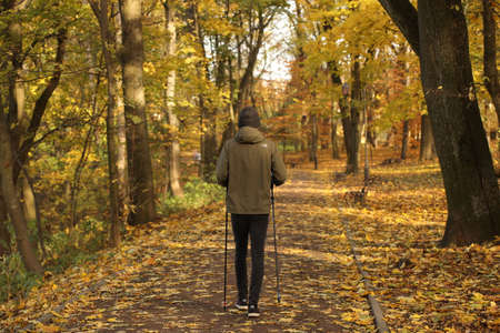 A young guy is engaged in Nordic walking in an autumn park among fallen yellow foliage. The physical activity of a healthy lifestyle. Change of seasons. Wilted nature. An abundance of warm colors.