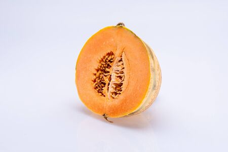 Melon sliced in half with visible seeds inside isolated in front of a white background