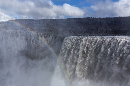 General view of Dettifoss, the most powerful waterfall in Europe. The sky is royal blue with clouds. We can distinguish the mist rising from the surface and a rainbow above