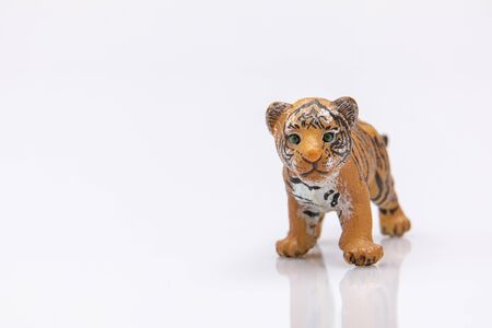 close up of a baby tiger from a plastic toy isolated on a white background