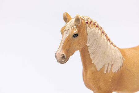 close up of a brown plastic horse head isolated on a white background