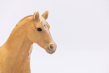 close up of a brown plastic horse isolated on a white background