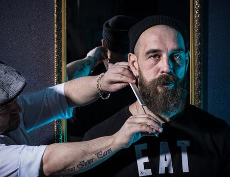 Barber cuts client beard