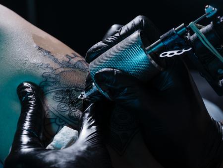 Close-up on tattoo machine make drawing on female leg 스톡 콘텐츠
