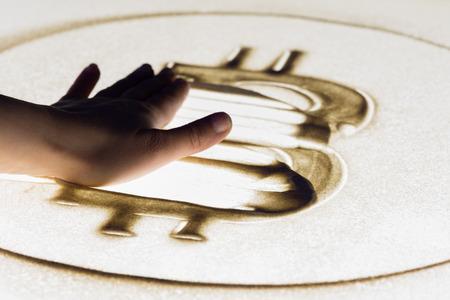 Erased bitcoin sign, sand painting on lightbox 스톡 콘텐츠
