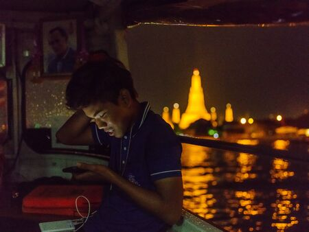 THAILAND, BANGKOK - APRIL 17, 2018: Thai teenager after sunset sails by express boat along the Chaopraya River near the Temple of the Dawn (Wat Arun). 에디토리얼