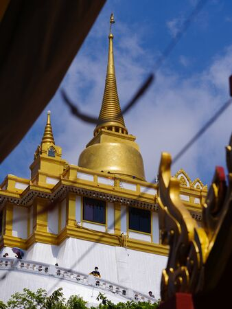 THAILAND, BANGKOK - APRIL 14, 2018: Artificial hill inside the Wat Saket in Bangkok, Thailand, the visitors climb the stairs of the temple. Phu Khao Thong is a popular Bangkok tourist attraction and become one of the symbols of the city.
