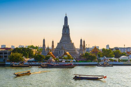 THAILAND, BANGKOK - APRIL 12, 2018: Early evening, the tourist boats sail along the Chaopraya River near the Temple of the Dawn. Wat Arun is a popular Bangkok tourist attraction and become one of the symbols of the city. 에디토리얼