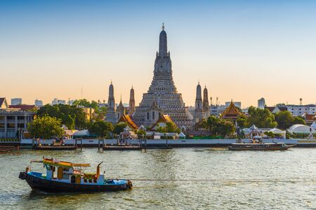 THAILAND, BANGKOK - APRIL 12, 2018: Early evening, the towboat sail along the Chaopraya River near the Temple of the Dawn. Wat Arun is a popular Bangkok tourist attraction and become one of the symbols of the city.