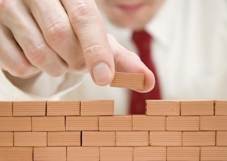 zaken man bouwen van een muur