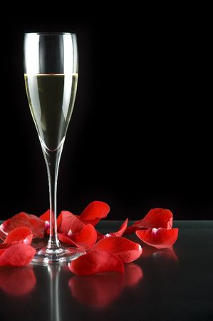 champagne flutes: champagne glass with petals of rose isolated on black background Stock Photo