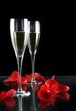 champagneflutes met bloemblaadjes van rose geïsoleerd op zwarte achtergrond