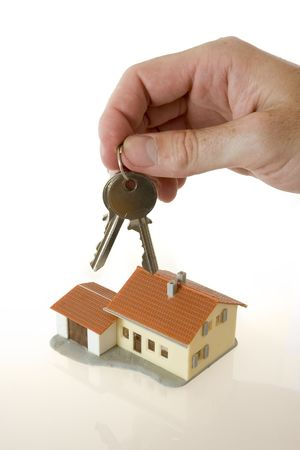 businessman hand with keys and a little house photo