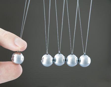 hand holding a pendulum ball