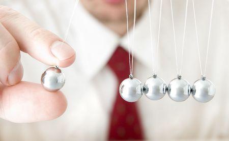 businessman hand holding a pendulum ball Stock Photo - 7669176