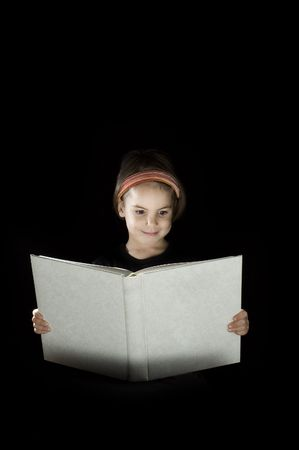 little girl reading a book isolated on black background Stock Photo - 7769979