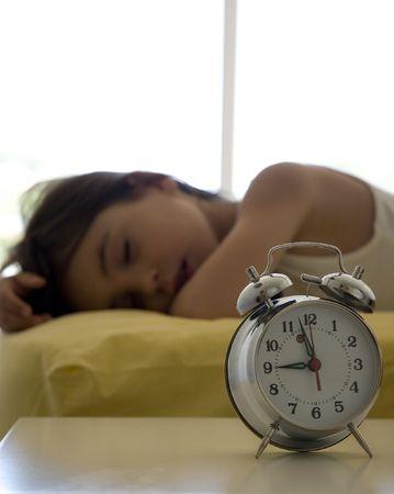 bambina sul letto con una sveglia Archivio Fotografico