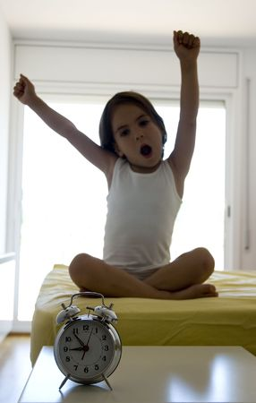 awaken: little girl on the bed with an alarm clock