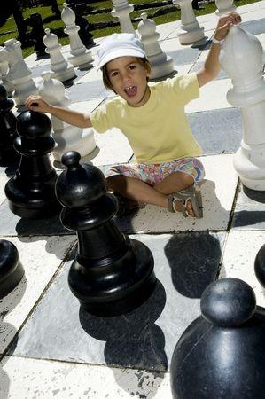 little girl playing lifesize chess photo