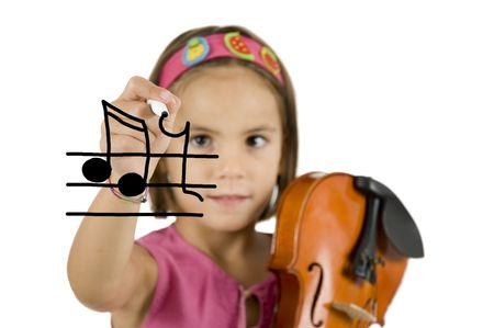 klein meisje houdt een pen en een viool geïsoleerd op wit Stockfoto