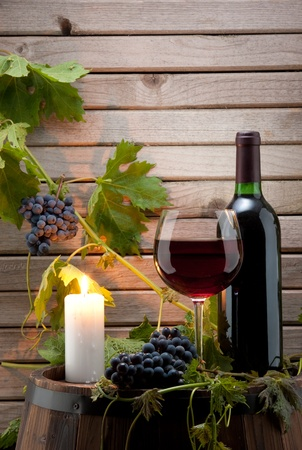 still life of wine: red wine bottle and glass with a candle background  Stock Photo