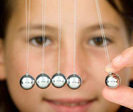 physics background: young girl holding a pendulum ball  Stock Photo