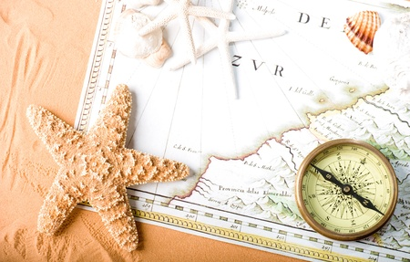 nautical star: Stock Photo: old map (Public domain - 1640 copyright expired) and compass on sand background