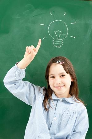 ni�os en la escuela: chica con pizarra y bombilla sobre su cabeza