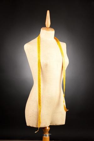 kleermakers mannequin met meetlint op zwarte achtergrond