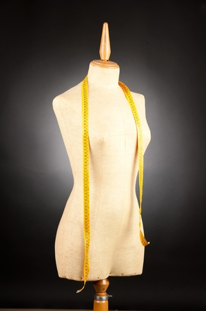 tailor mannequin with tape measure on black background  Stock Photo