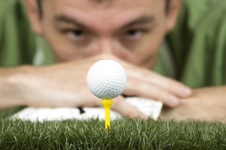 golf player looking at the ball on the tee photo