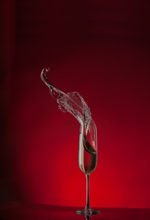 champagne flute splash isolated on red background Banque d'images