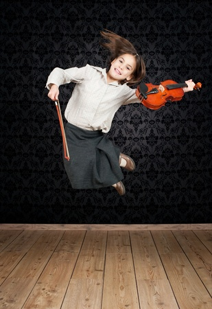 little girl with violin jumping photo