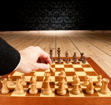 maneuver: businessman hand holding a pawn from a chessboard
