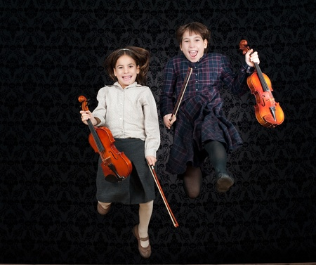 two girls with violins jumping Banco de Imagens