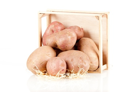 heap of potatoes on a wood box on white background Stock Photo - 12173707