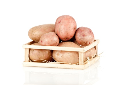 heap of potatoes on a wood box on white background photo