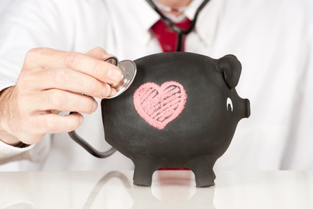 businessman with stethoscope on a piggy bank photo